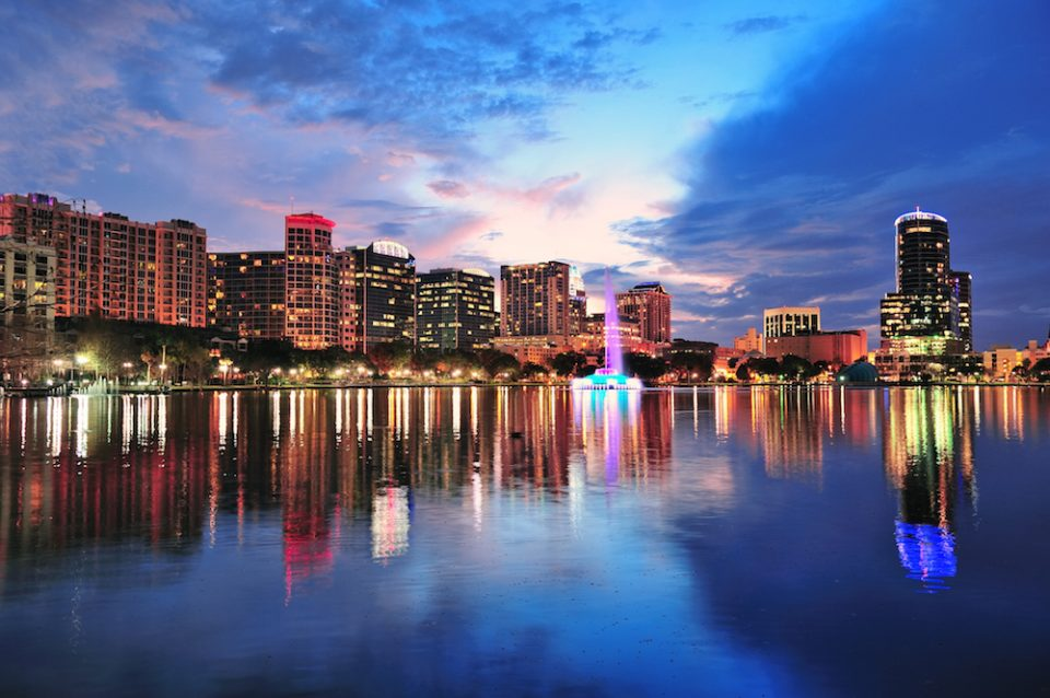Orlando downtown skyline over Lake Eola at dusk with urban skyscrapers and lights.