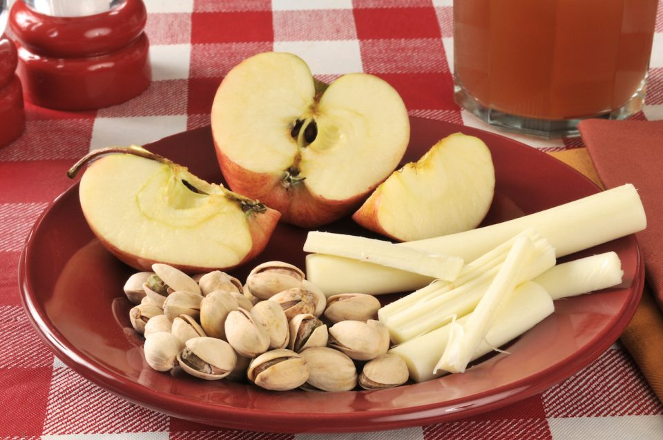 a healthy snack with pistachios string cheese apples and a glass of juice