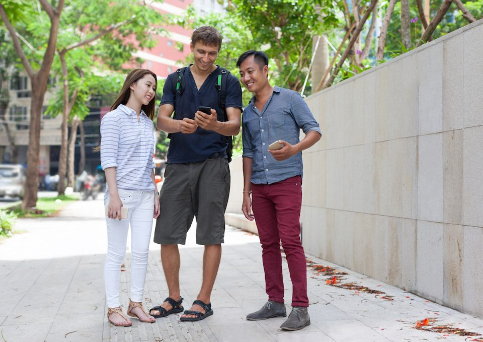 Asian couple help tourist cell smart phone caucasian man