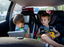 Two kids in the car playing games