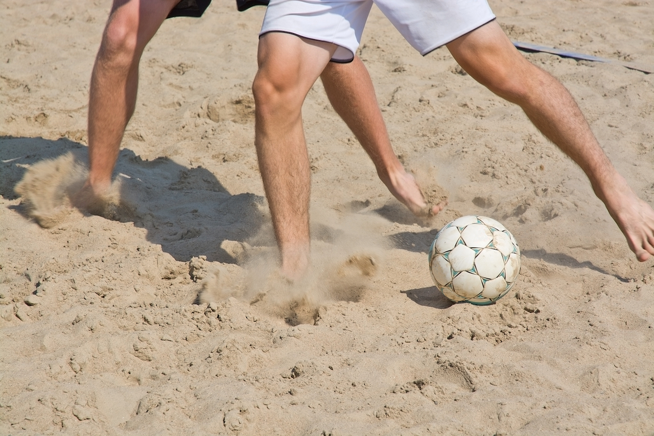 close up of mens legs playing beach soccer