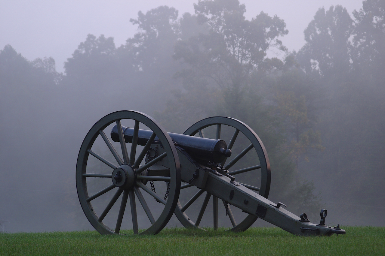 civil war cannon in a field on a foggy day
