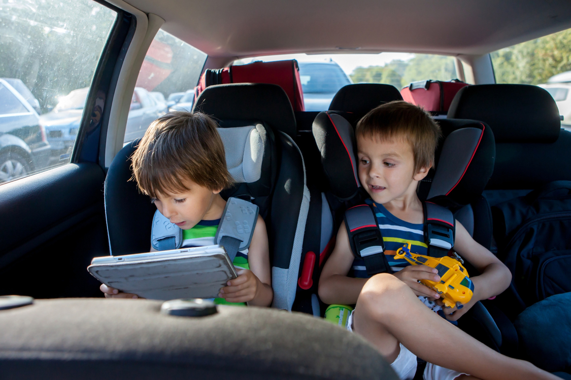 Two young boys traveling by car and playing with a tablet
