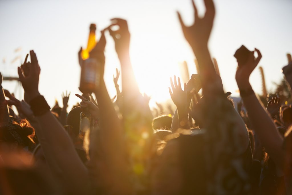 crowd holding their hands in the air during sunset at an outdoor musical festival