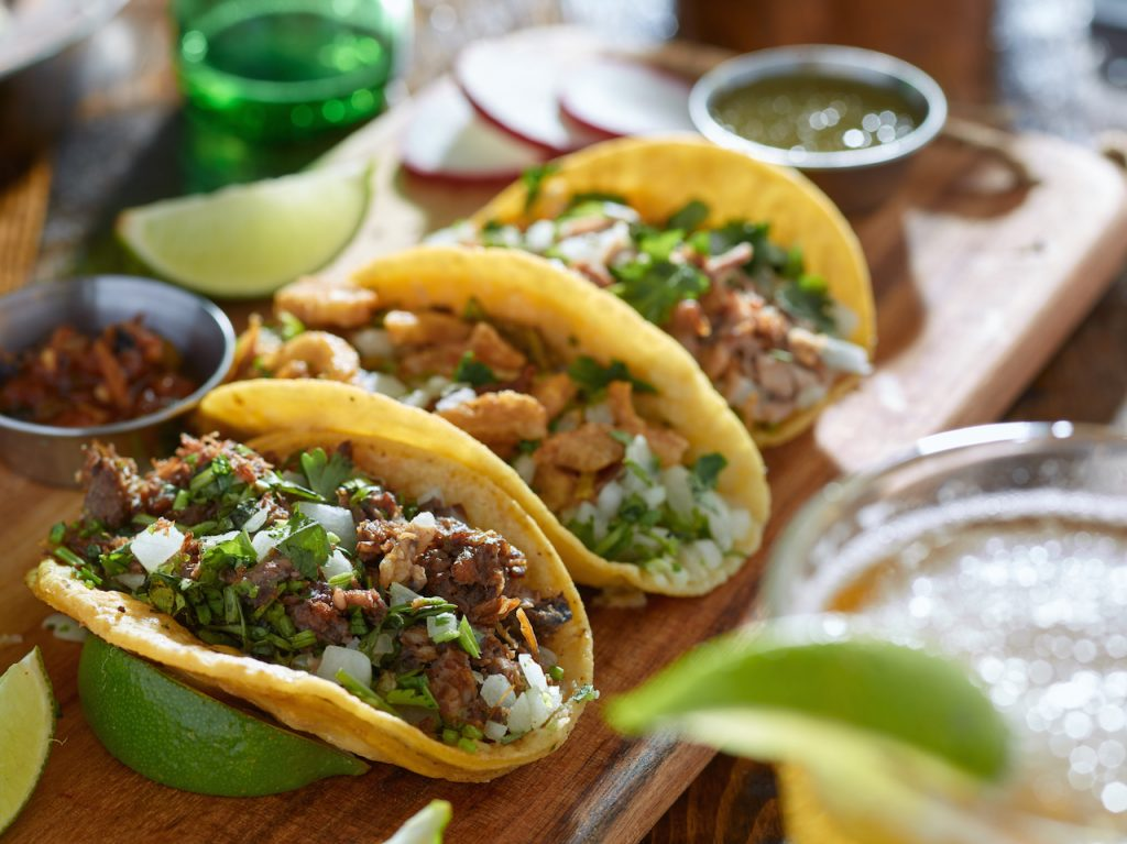 three mexican street tacos topped with fresh cilantro and lime wedges in the background