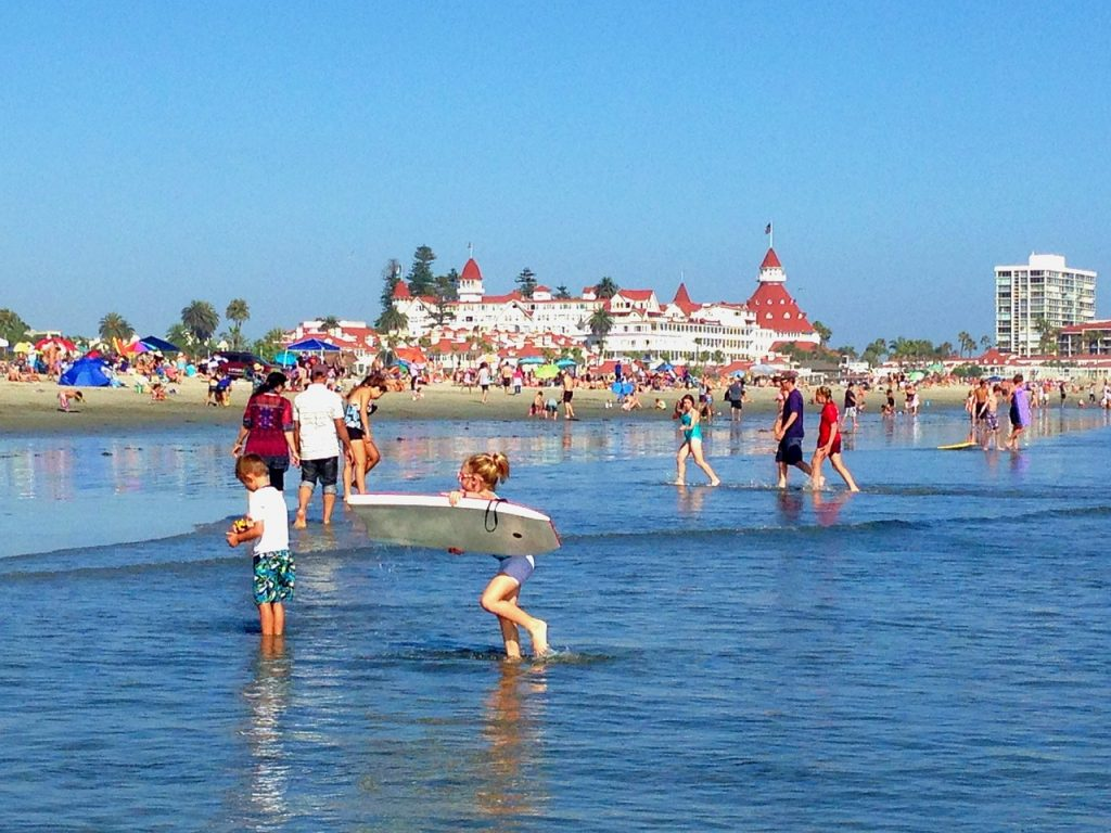 You and old people playing and walking in the water on Coronado Beach, San Diego