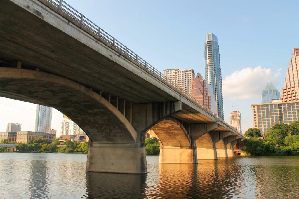 underside view of the Congress Avenue bridge stretching across the Colorado River in Austin, Texas