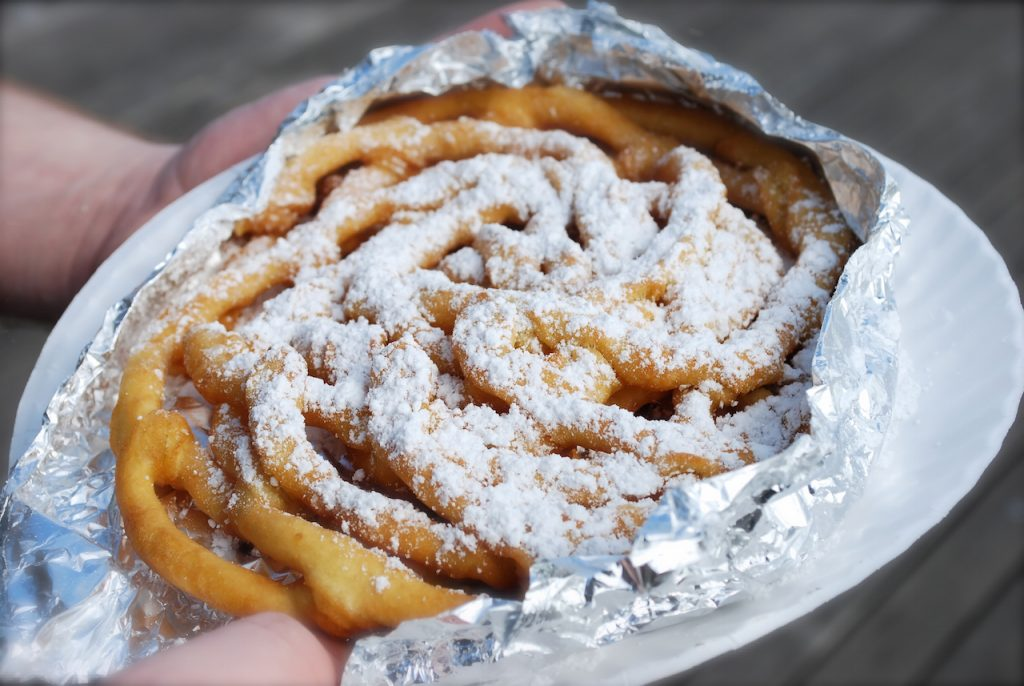 fresh funnel cake, wrapped in foil, on a paper plate, topped with white powdered sugar