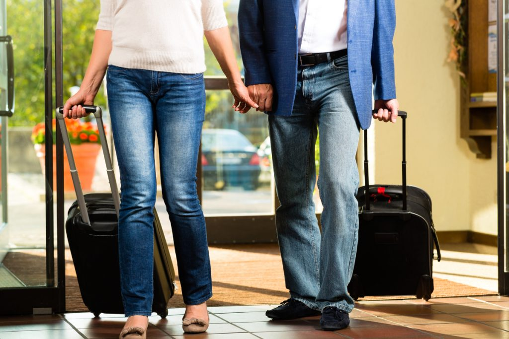 close up of an older couple holding hands and wheeling suitcases into a hotel lobby or airport