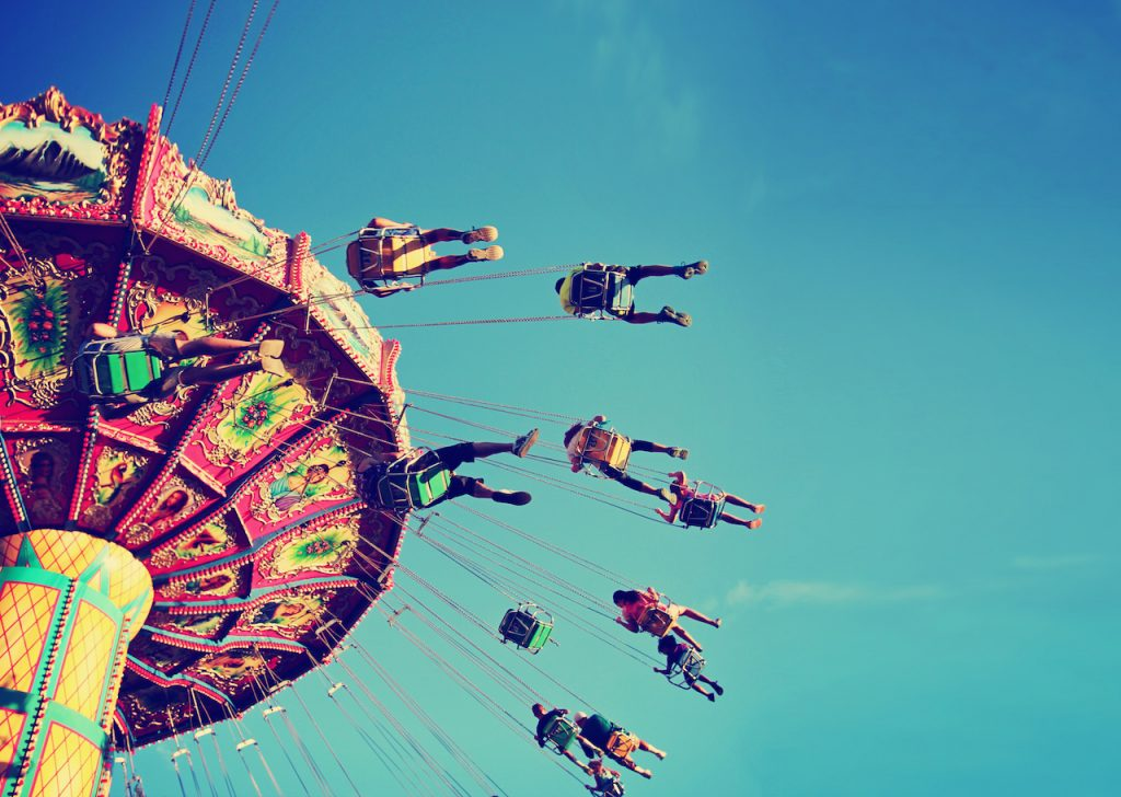 underview of people in the air on a giant fair swing, photo is taken with a warm vintage filter