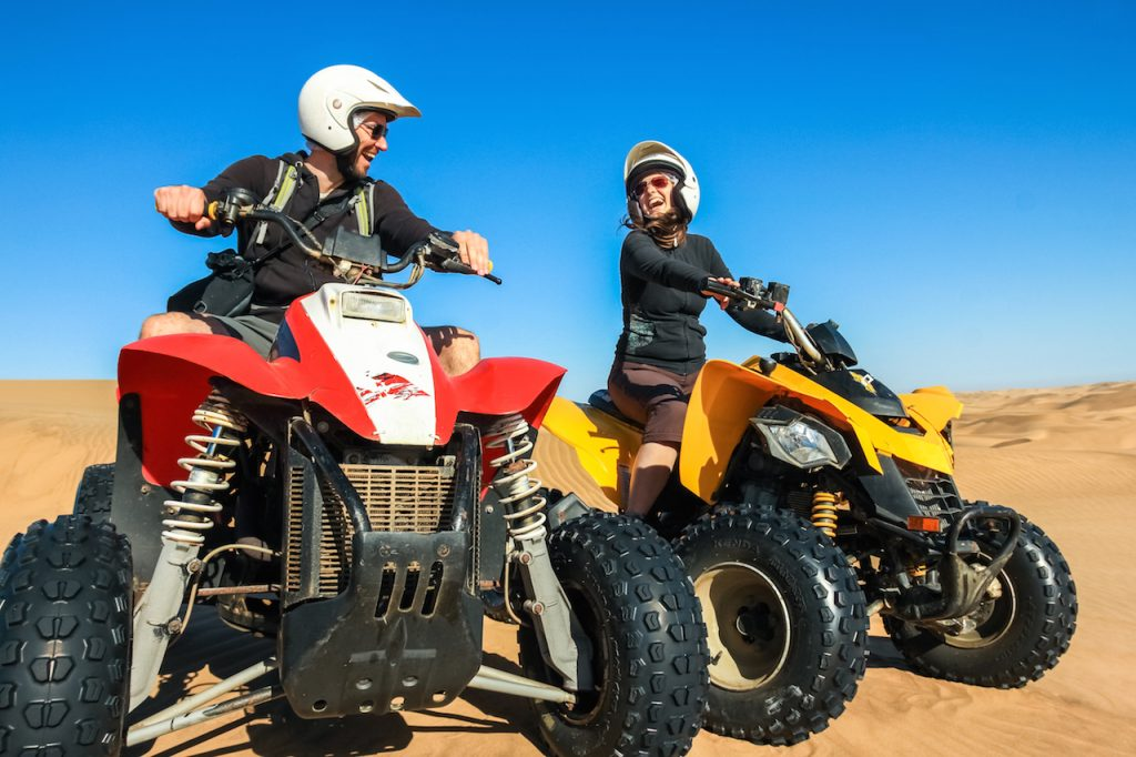Happy couple of quad bikers laughing joyful, cheerful and fresh. Young active caucasian couple in outdoor activity driving quad ATV in Namib desert, Namibia, Africa.