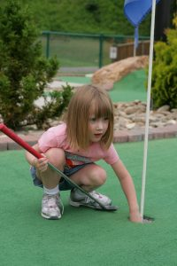 Four year old child playing mini golf