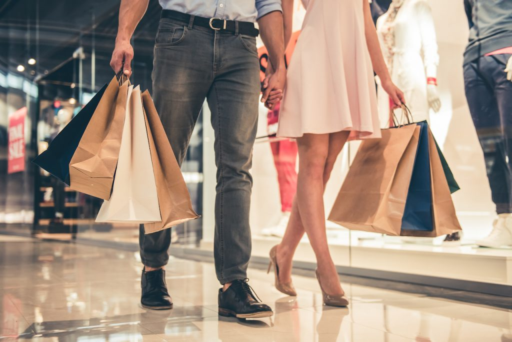 Cropped image of beautiful couple with shopping bags doing shopping in the mall
