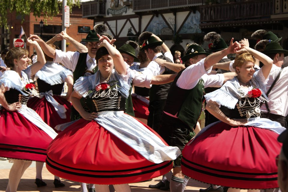 a group of dancers perform German folk dance on front street during a Mai-fest, in Leavenworth, Washington, USA
