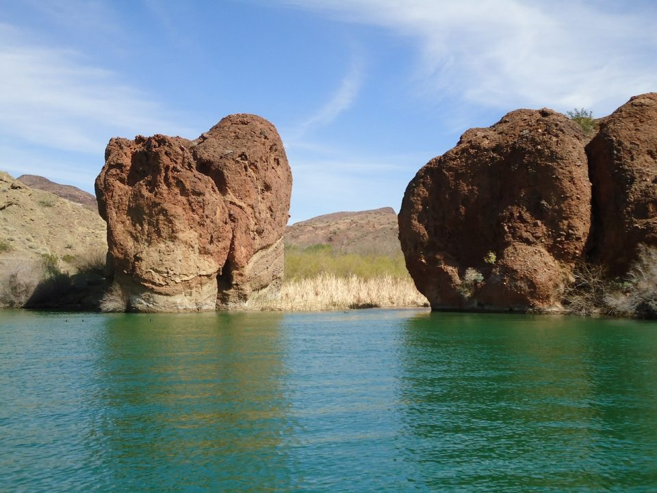 clear blue, green water on Lake Havasu with giant rocks and blue skies in the background