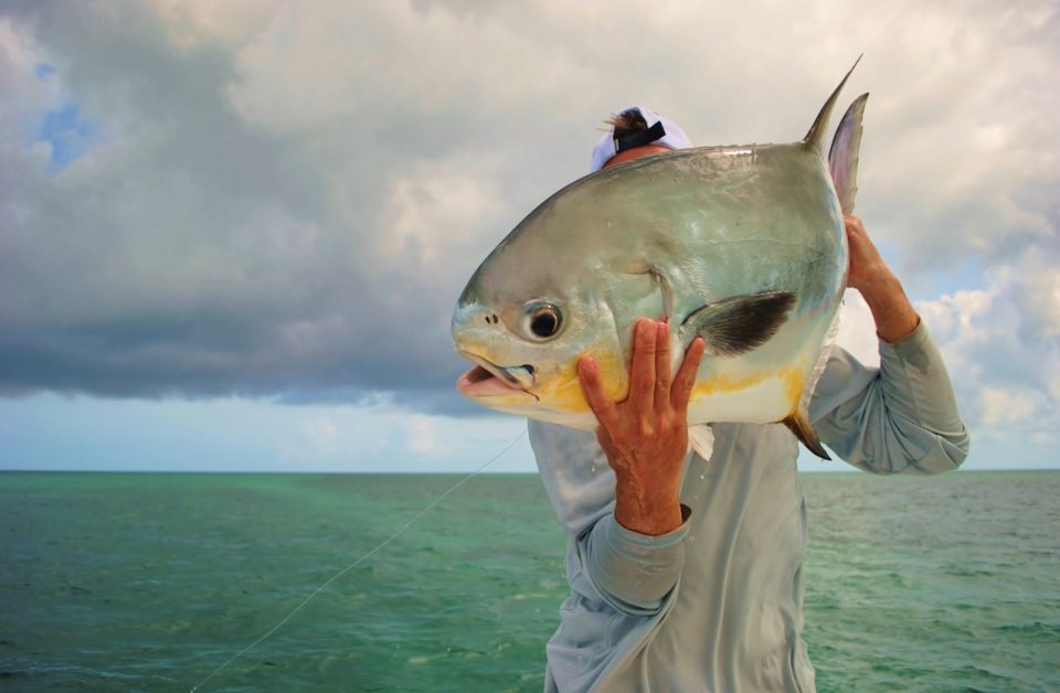 Man holding up giant permit fish he caught in the florida keys