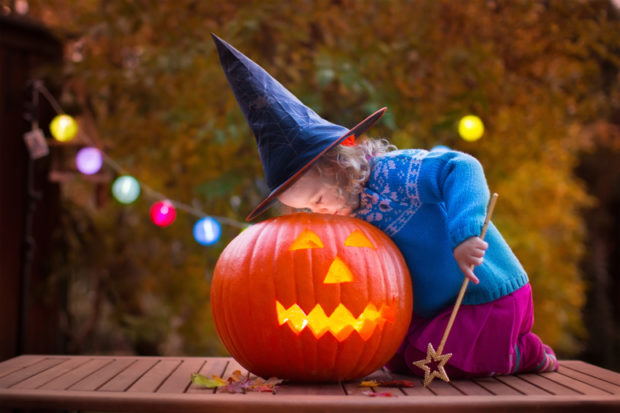 Girl with witch hat and wand looking inside of a lit jack o lantern