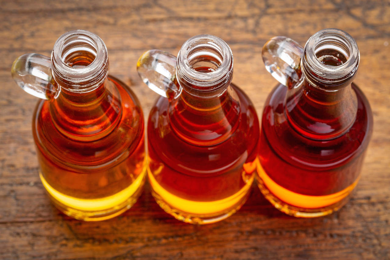 three glass small glass bottles of maple syrup against rustic wood