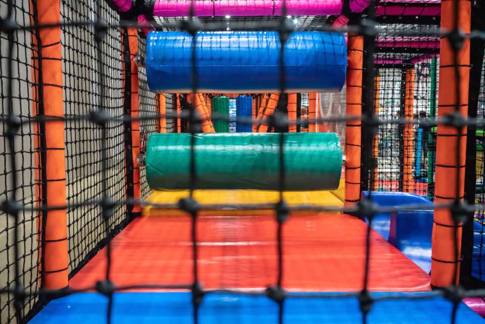 Kids playground for gym with slide and maze in kindergarten. Modern children playground indoor. Inside the colorful plastic jungle for playing and development of motor skills.