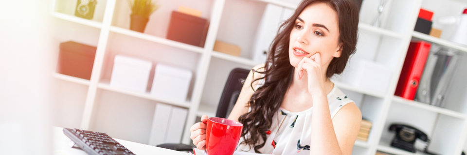 Beautiful young girl sits at office desk, looks at computer screen and holds a red mug in hands.