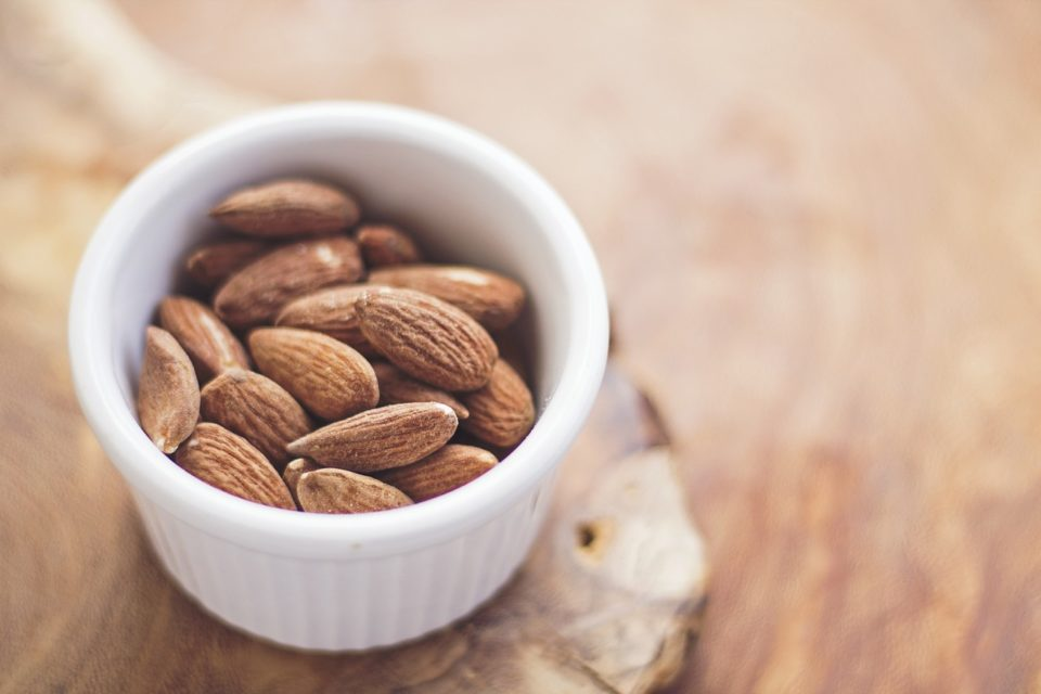 white ramekin filled with almonds on wooden background