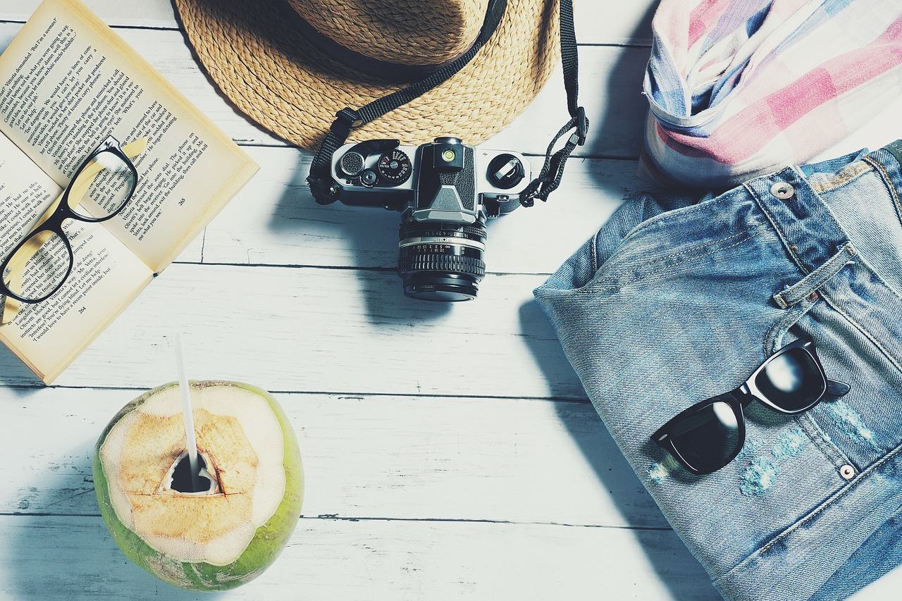 camera, book, glasses, and a coconut on a table