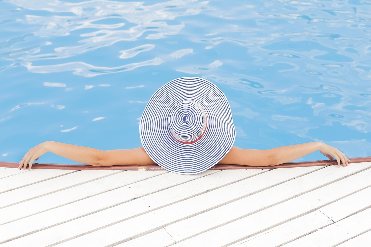 women with a hat lounging at the pool