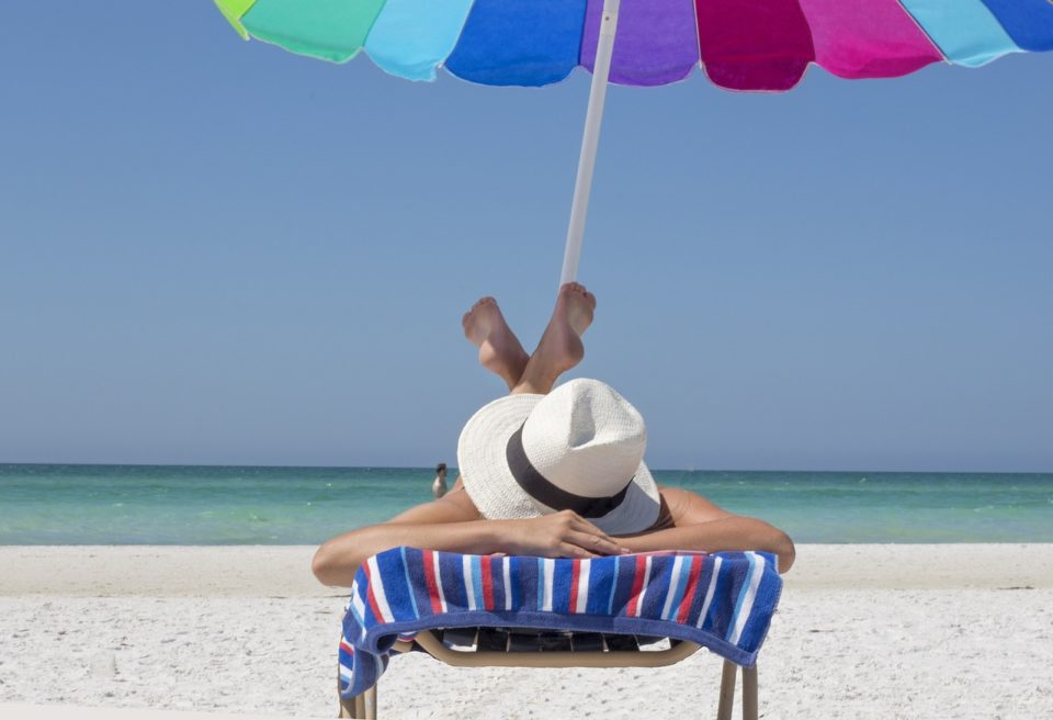 woman napping under a colorful beach umbrella