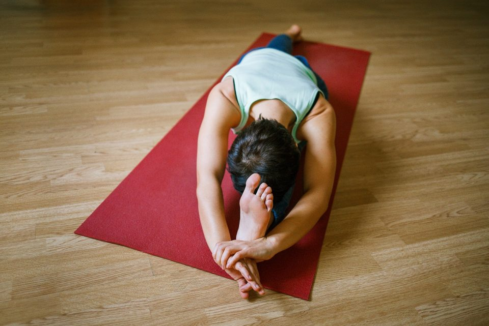woman practicing yoga on a red mat