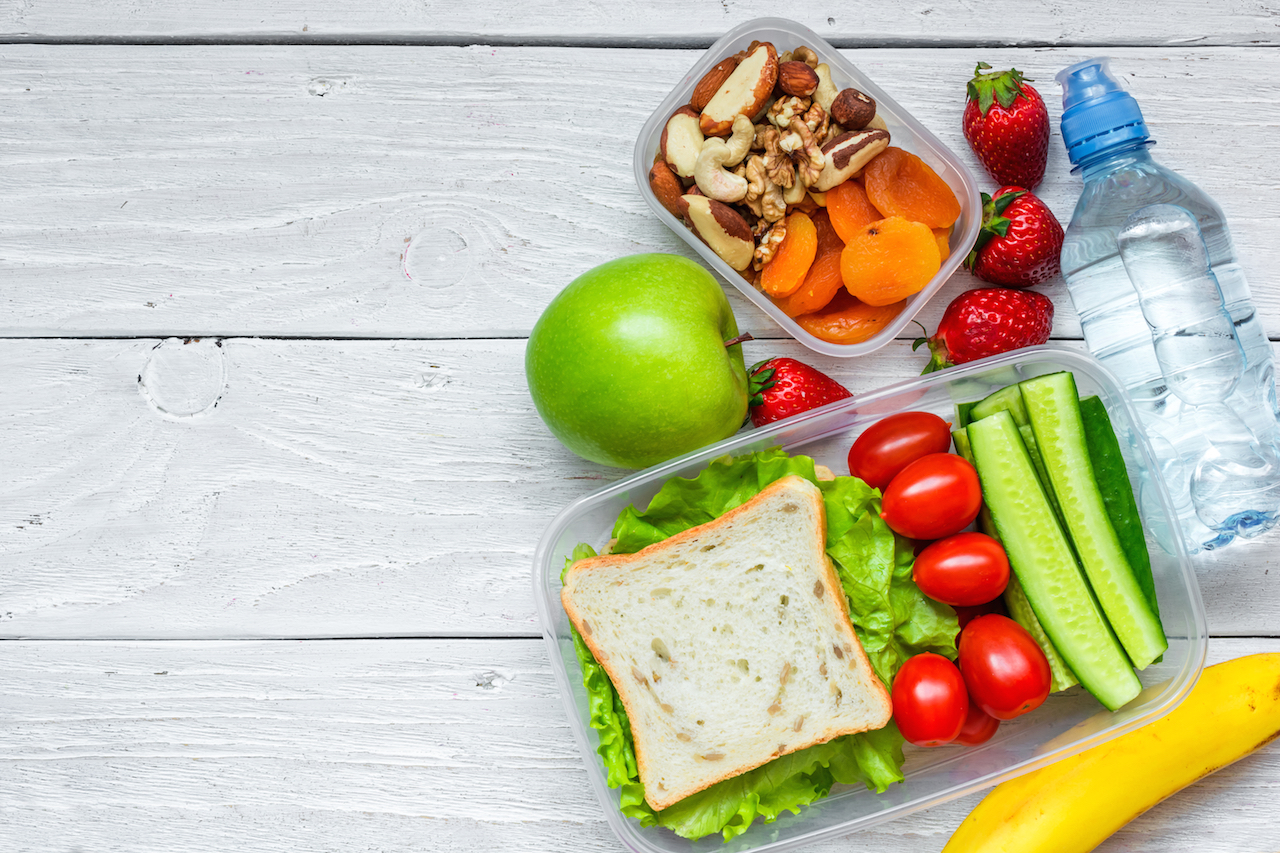 school lunch boxes with sandwich and fresh vegetables, bottle of water, nuts and fruits on white wooden background