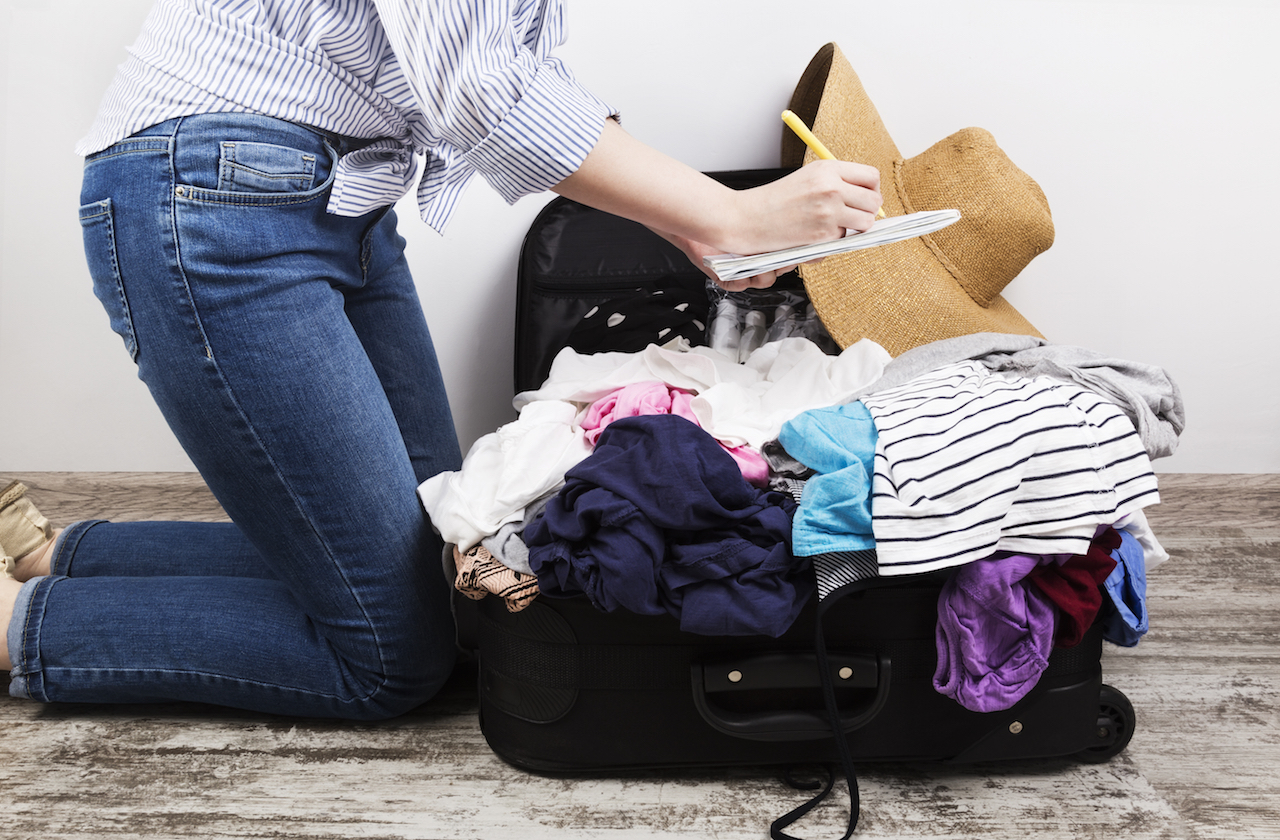 woman packing an overflowing suitcase