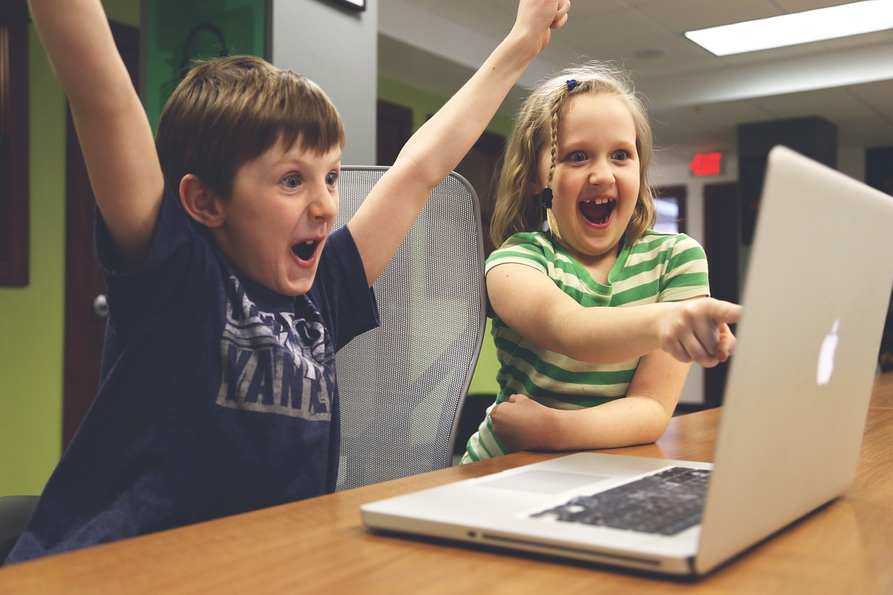 excited kids looking at the computer screen