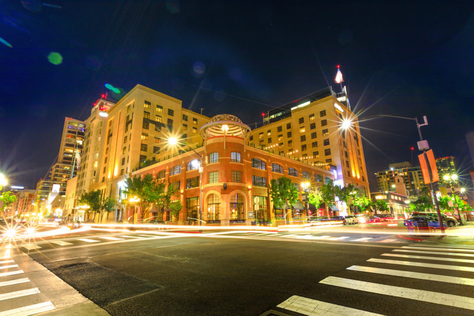 Historical building corner on Fifth Avenue, the main street of the Gaslamp Quarter, in the Historic District of Downtown of San Diego, California, United States by night. Light trails effect.