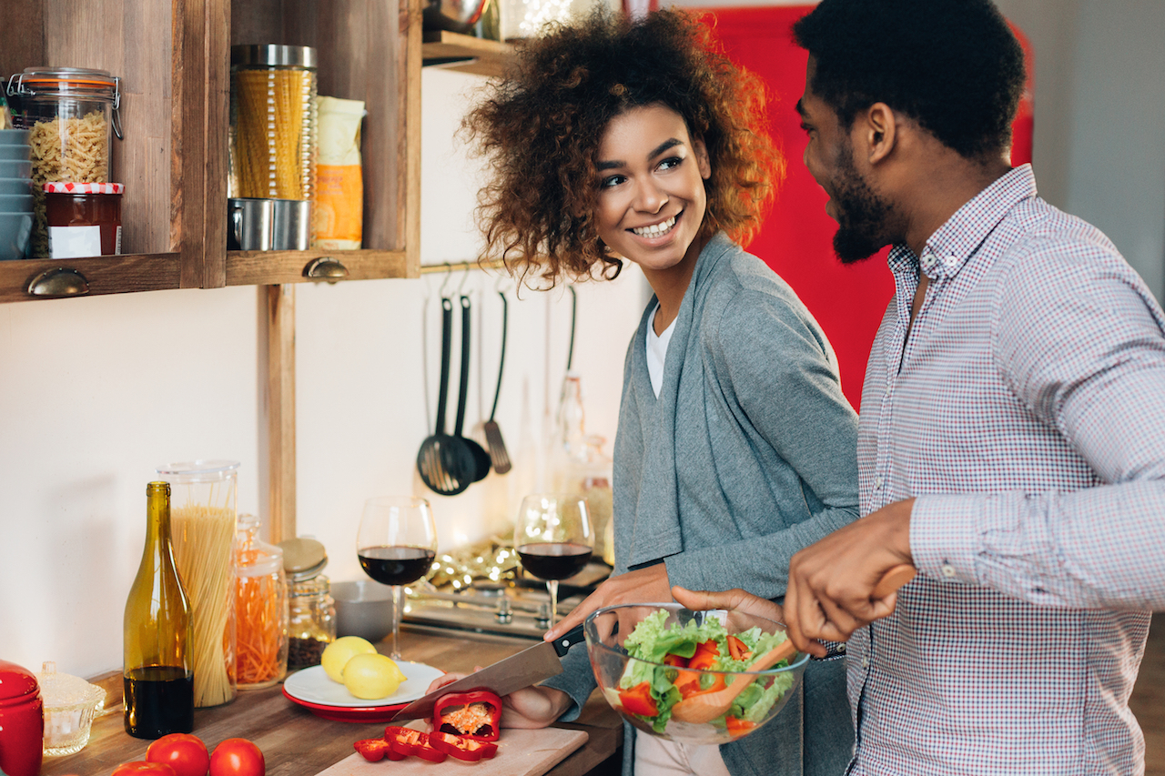 young, attractive couple cooking together in their kitchen