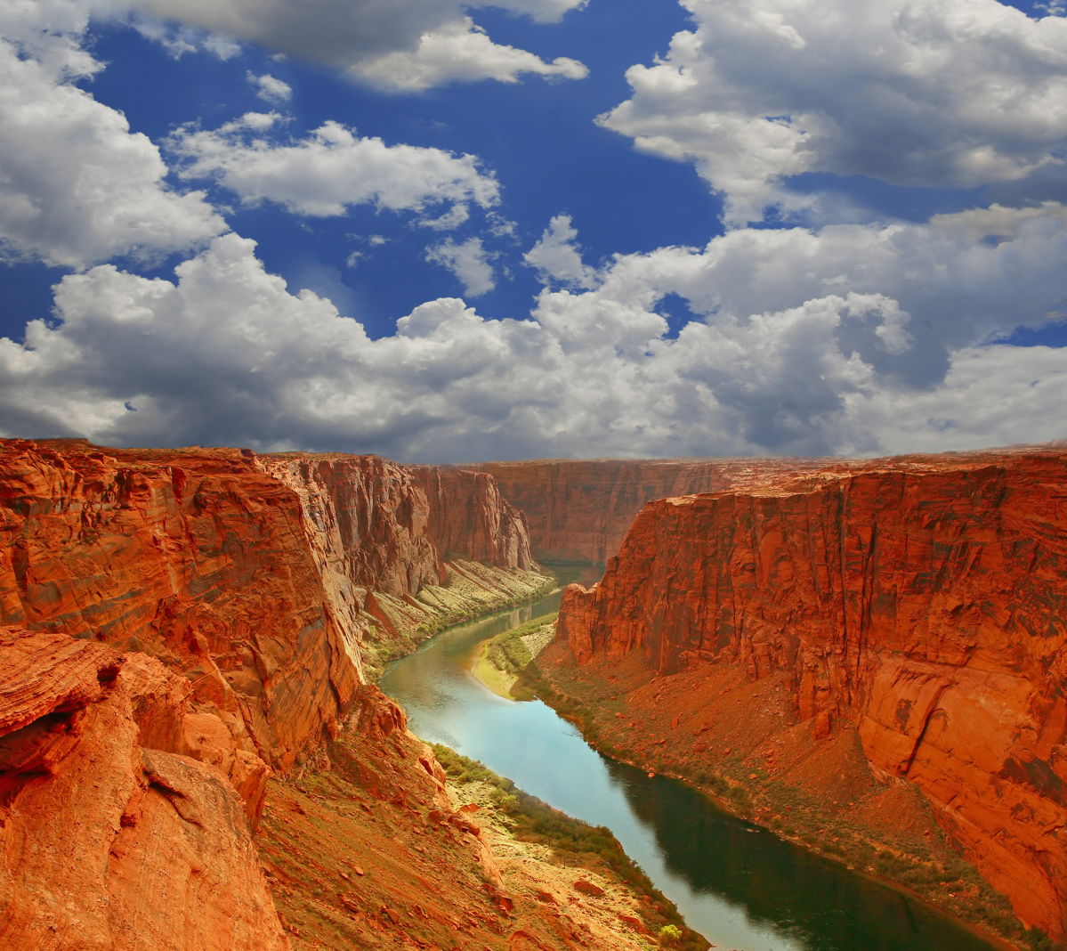 orange walls in the Grand Canyon on a bright blue day, white clouds in the sky