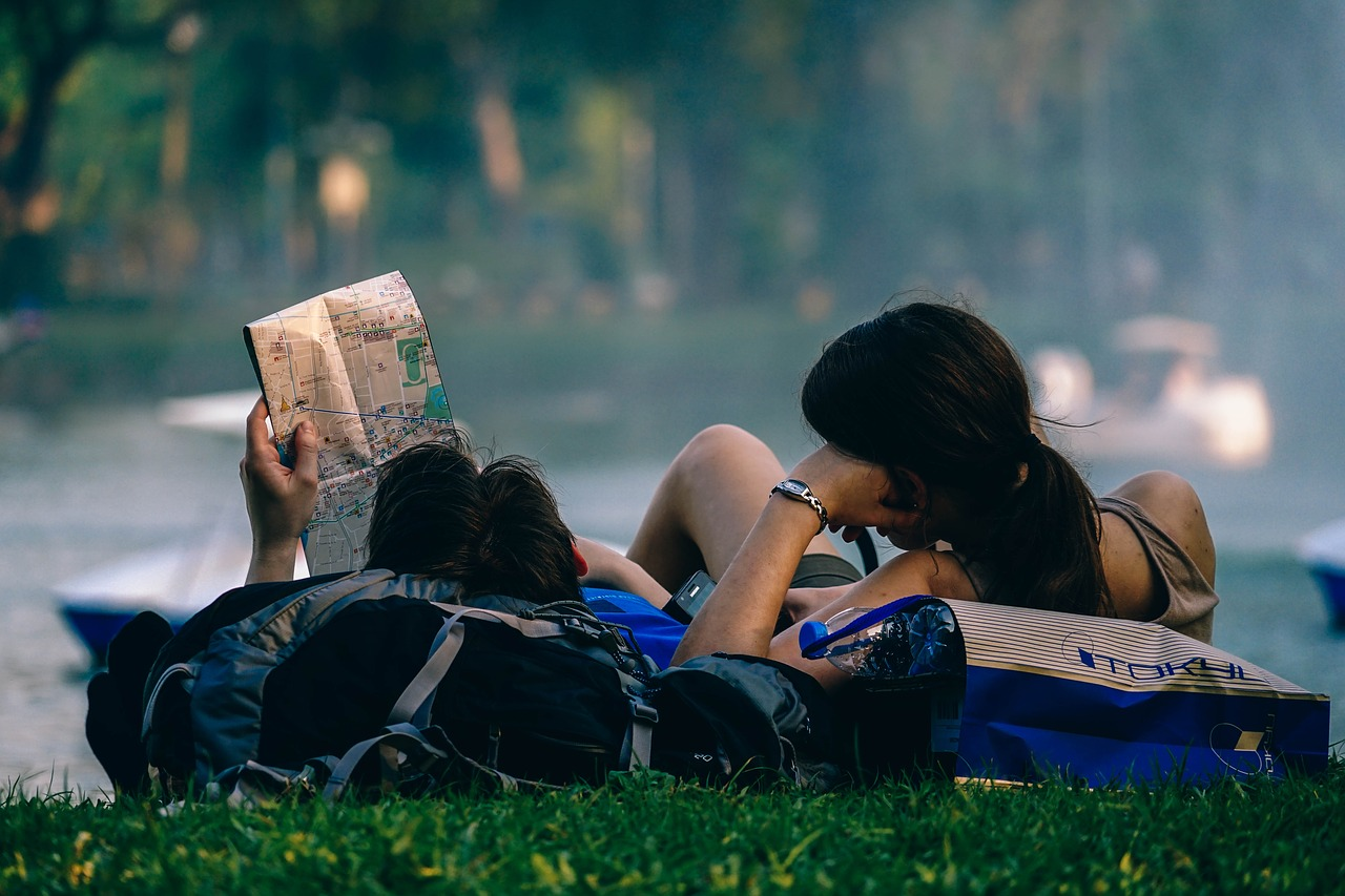 young couple laying in q shady grassy area, looking at a travel map together