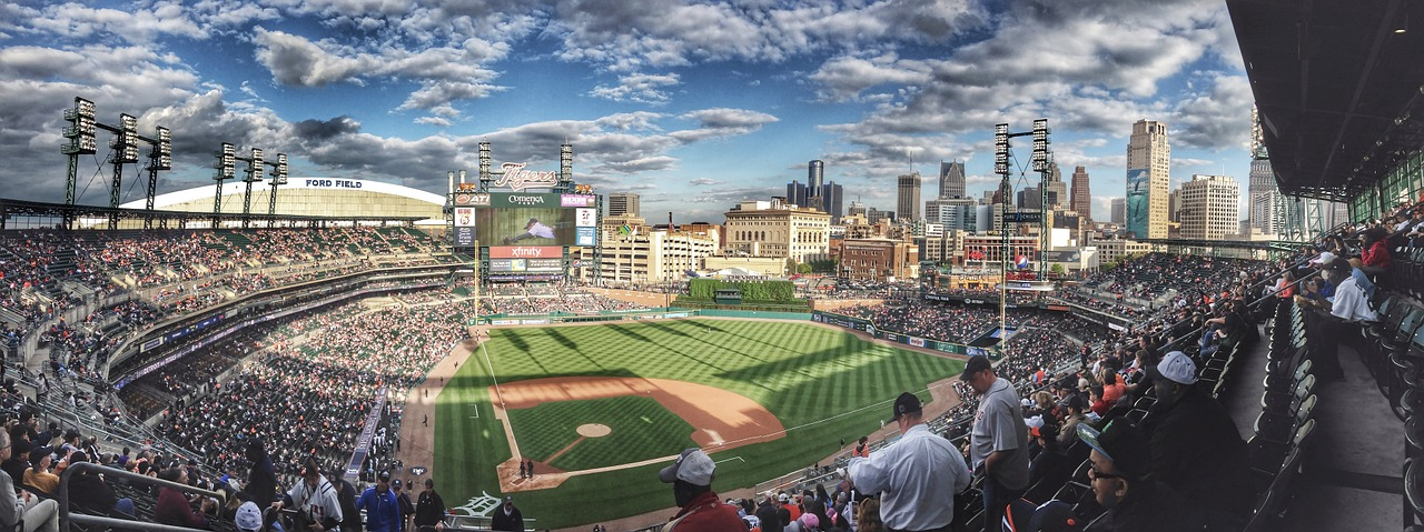 panoramic view of a packed baseball stadium and field with blue skies and clouds