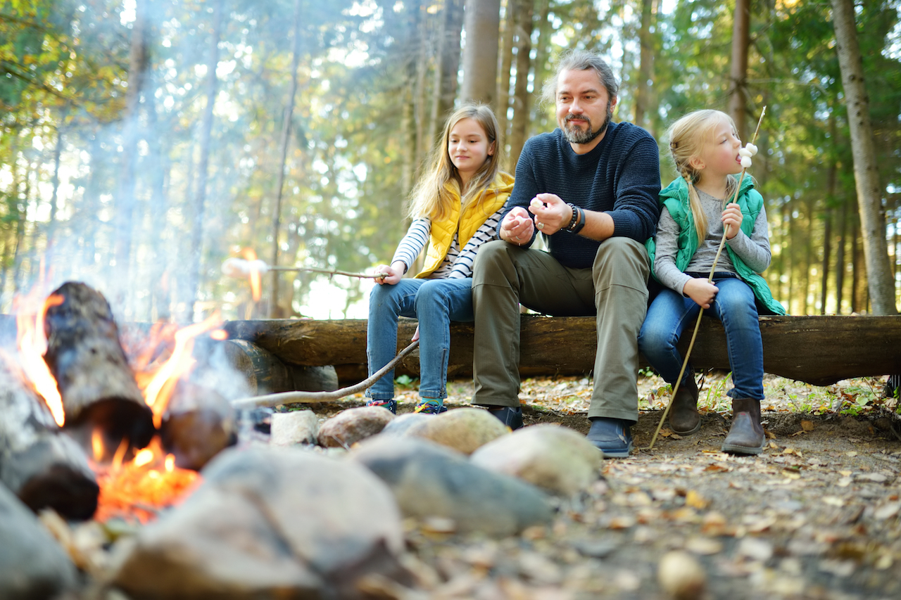 two young girls sitting at a campfire and roasting marshmallows with their dad