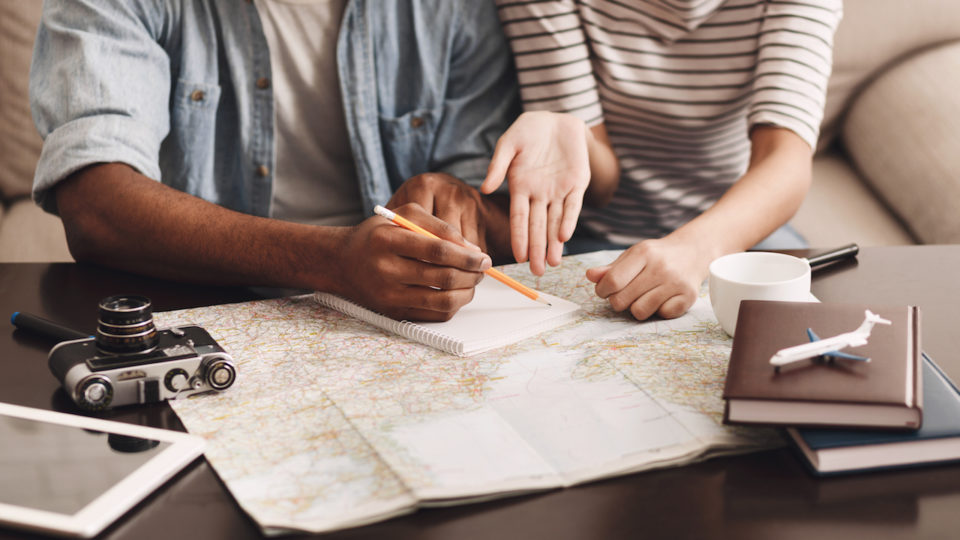Couple planning vacation and making notes in a diary