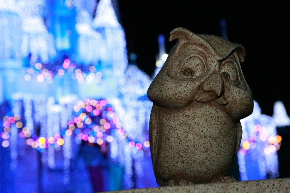 close up of cartoon character statue with lit up Disneyland castle in the background.