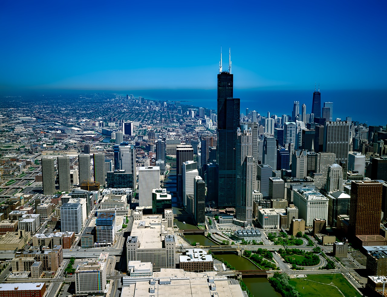 The Willis Tower in Chicago, Illinois, standing next to other buildings and a blue sky in the background