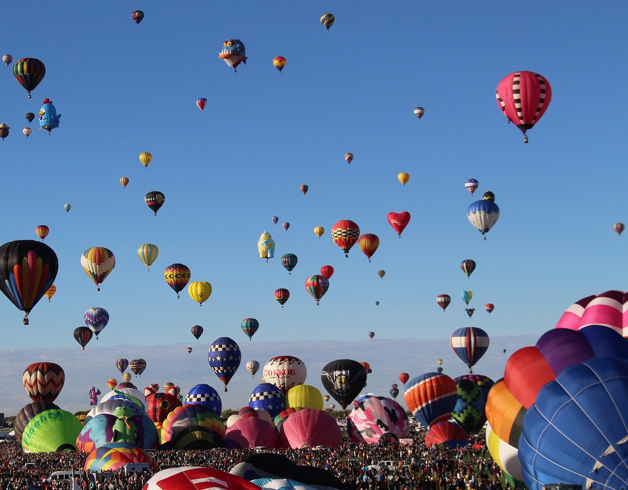 colorful hot air balloons taking off and floating in the blue sky at an outdoor festival
