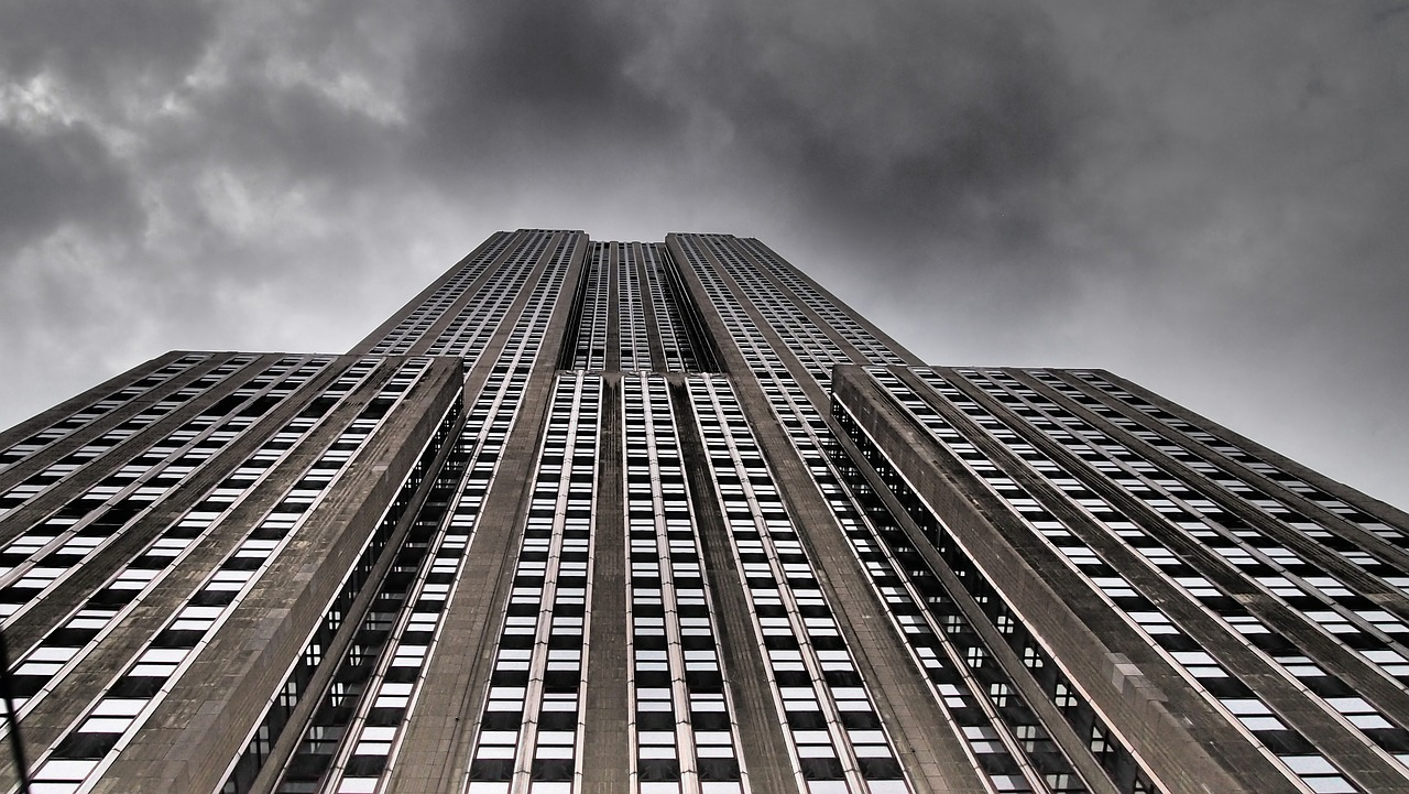 Upward view of the Empire State Building, grayish photo with visible thunderclouds