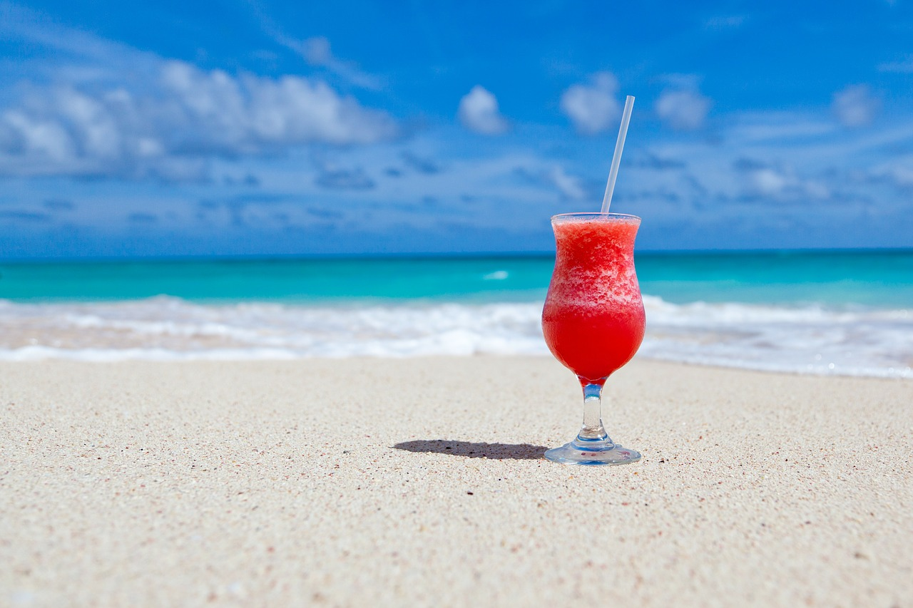 frozen red alcoholic beverage sitting on the beach sand on a bright blue day