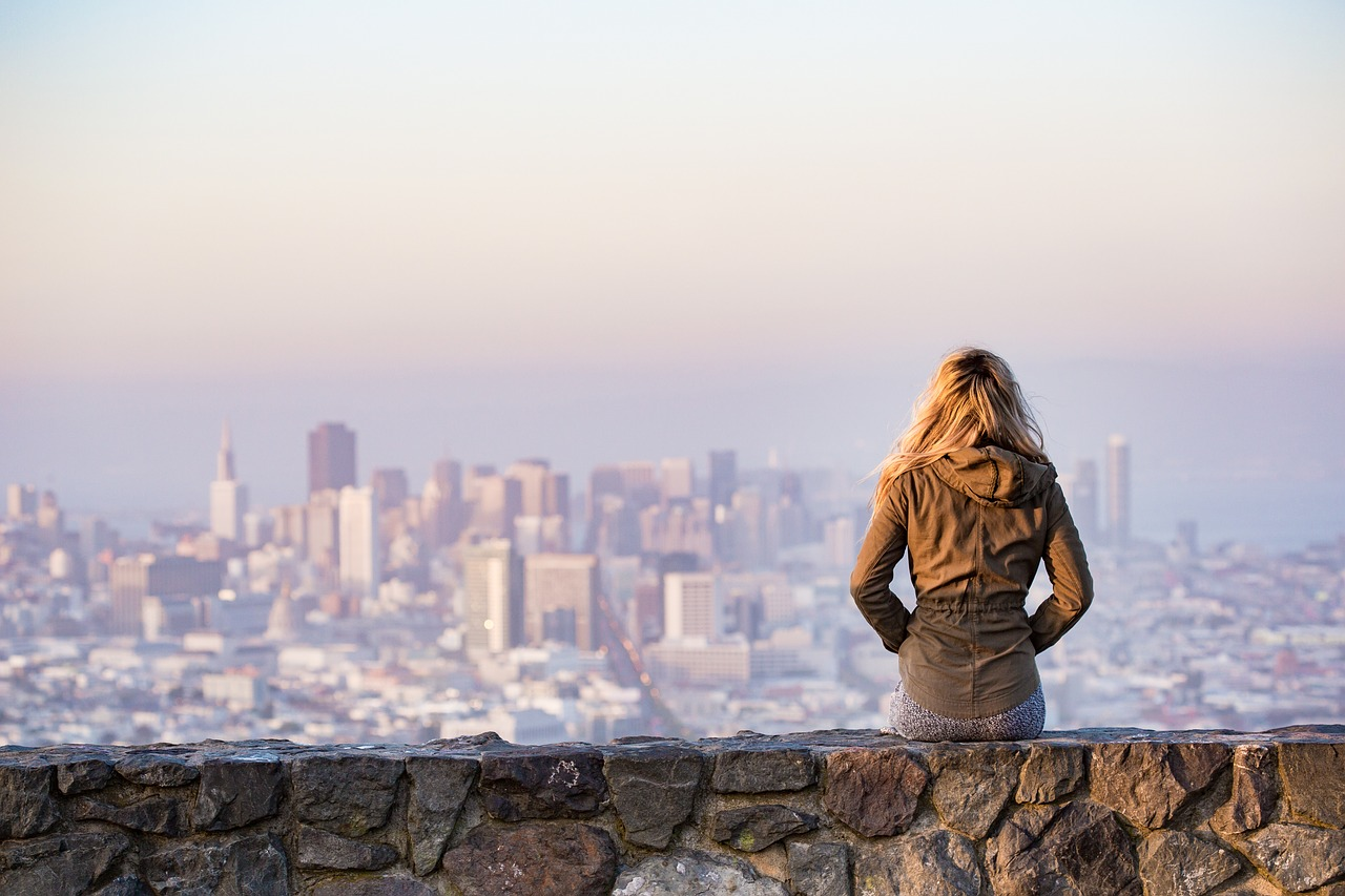 young blonde female traveler, looking at the city in the distance