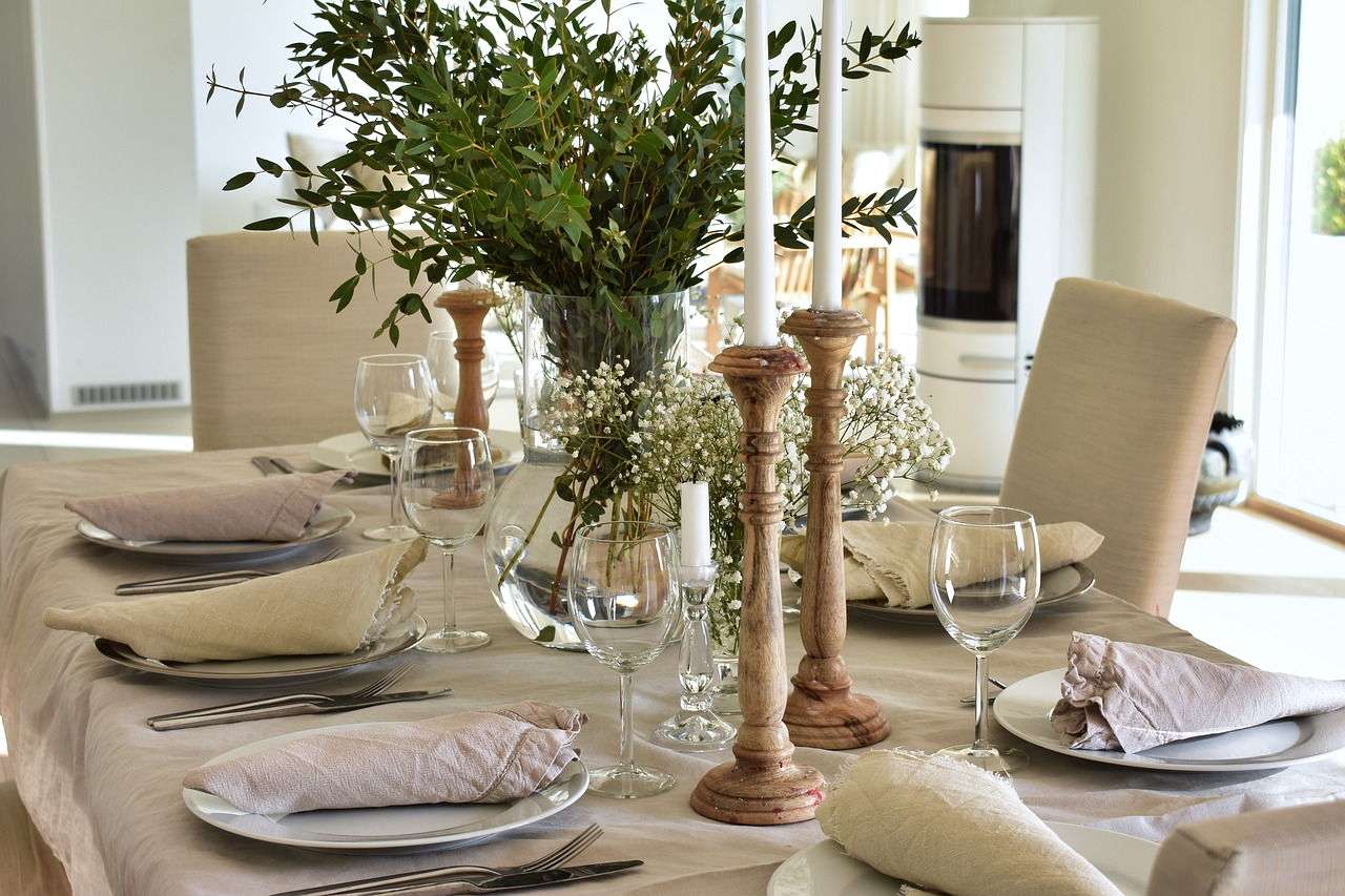 beautiful dinner party setting with white tablecloth, white napkins, candle fixtures and greenery