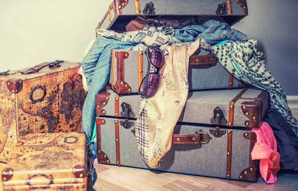 women's suitcases stacked on each other with scarves and sun glasses hanging out