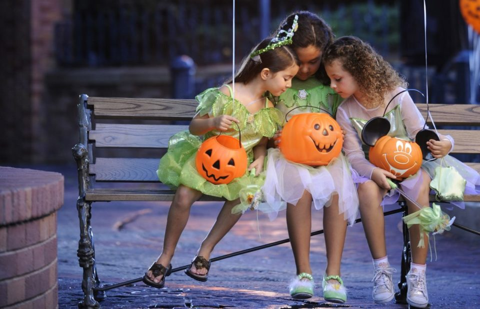 Three small girls looking into a halloween pumpkin while sitting together on a bench inside of Disney World