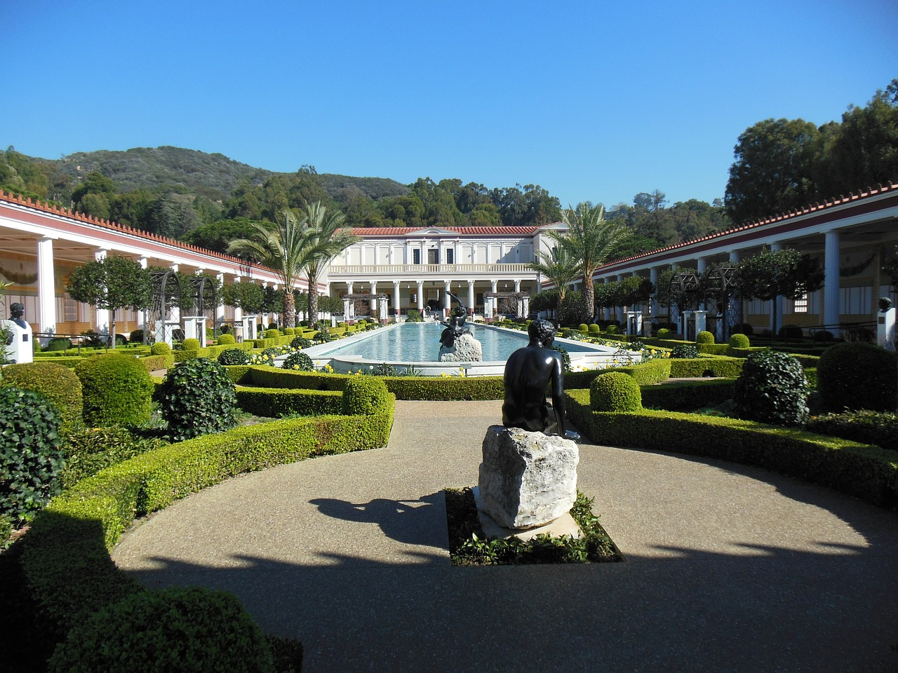 view of The Getty Villa with statues, a building and a pool