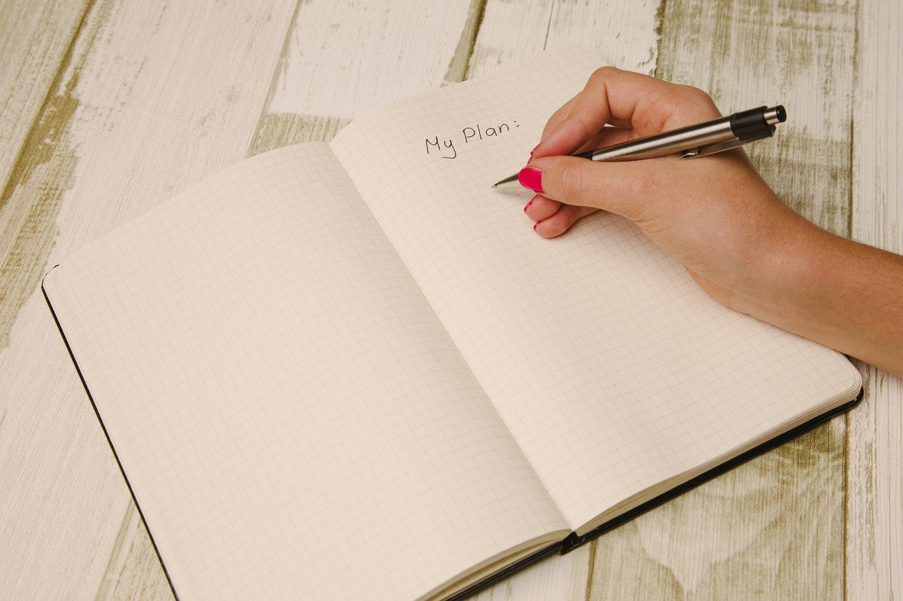 Woman writing a plan in her notebook